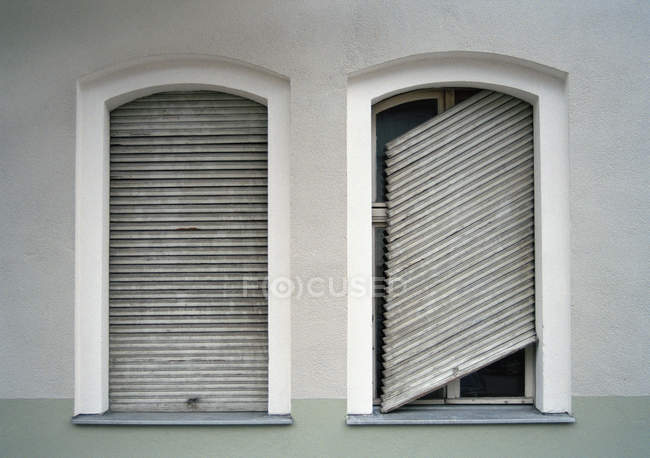 Two shuttered windows with one shutter broken — Stock Photo