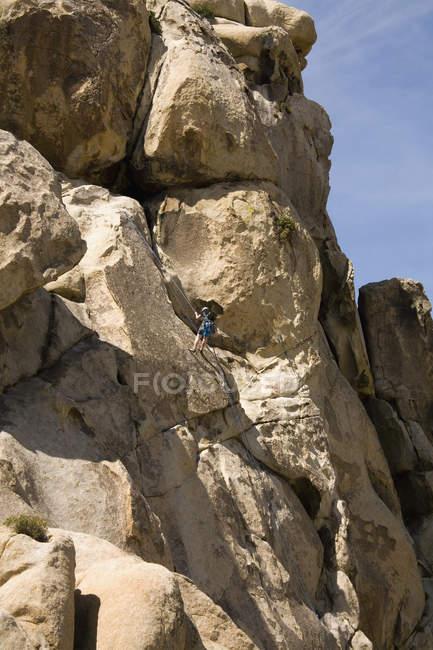Далеких зору людини альпінізм кам'янистій скелі — стокове фото