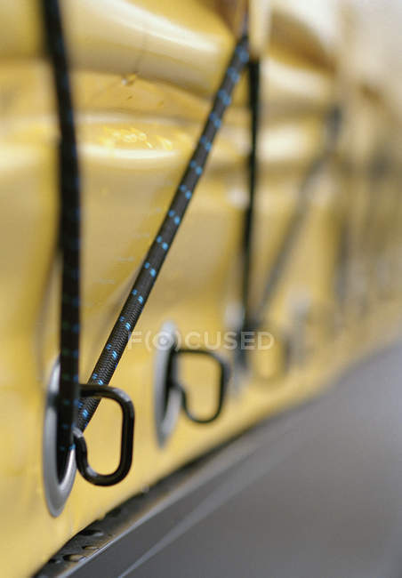 Vista de cerca de las cuerdas elásticas que aseguran la cubierta de plástico - foto de stock