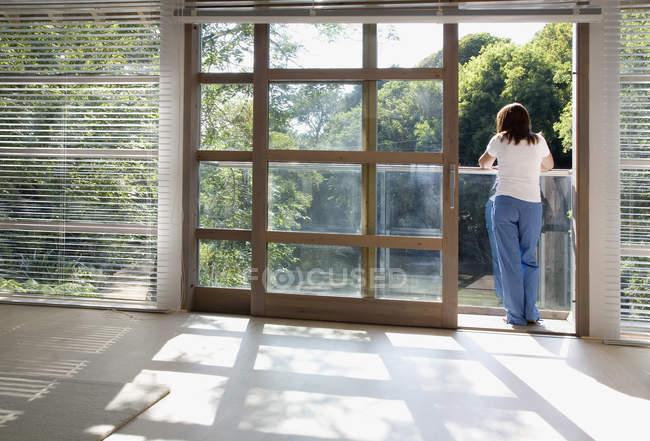 Quarto vazio, com a mulher na varanda iluminada pelo sol — Fotografia de Stock