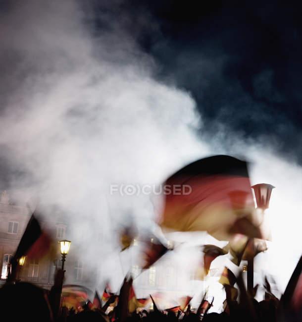 Verschwommene Aufnahme des Menschen winken deutsche Fahnen in der Nacht — Stockfoto