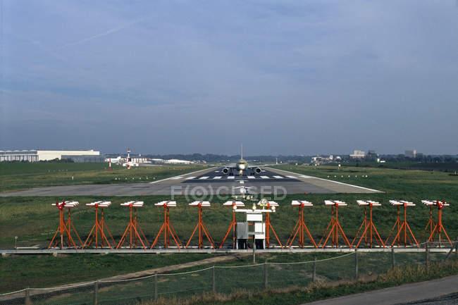 Вид спереди самолет посадки на взлетно-посадочной полосы в аэропорту — стоковое фото