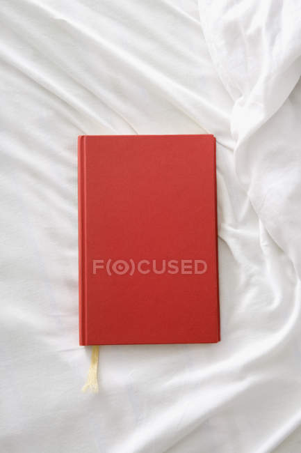 Directly above red book on white sheet — Stock Photo