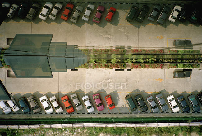 Припаркованные автомобили, отражающиеся в фасаде высотного здания — стоковое фото