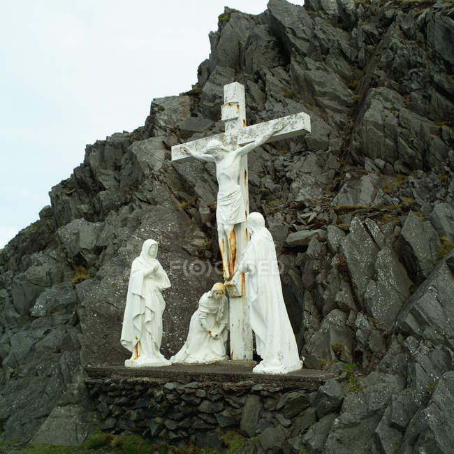 Stone crucifix and statues on rock formations — Stock Photo