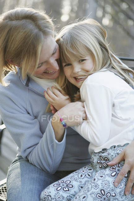 Mother and daughter embracing in a back yard — Stock Photo