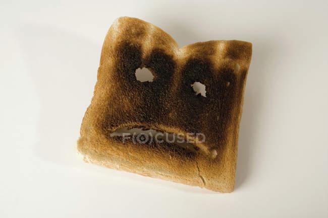 Ця частина спалені тосту з сумне обличчя — стокове фото