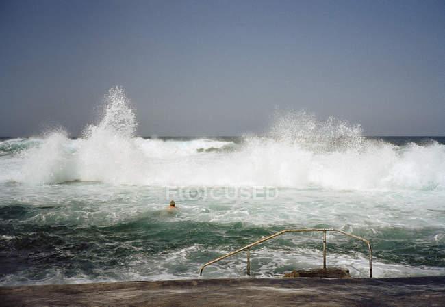 Vista distante da pessoa nadando em ondas de bater — Fotografia de Stock