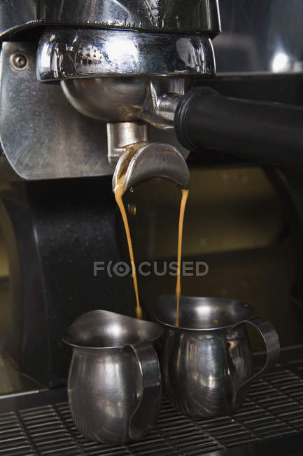 Coffee maker pouring coffee in two metal jags — Stock Photo