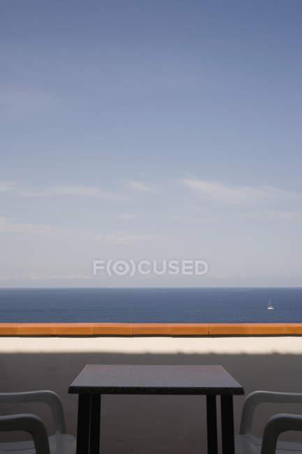 Tisch und Stühle auf dem Balkon über dem ruhigen Meer — Stockfoto