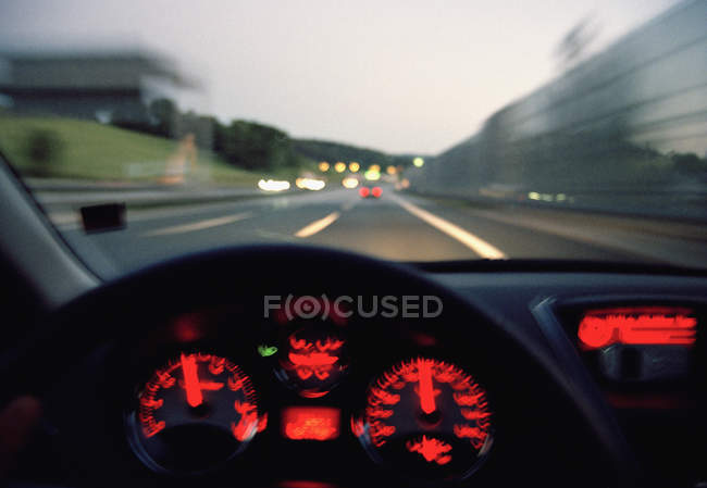 Illuminated dashboard of car driving on highway — Stock Photo