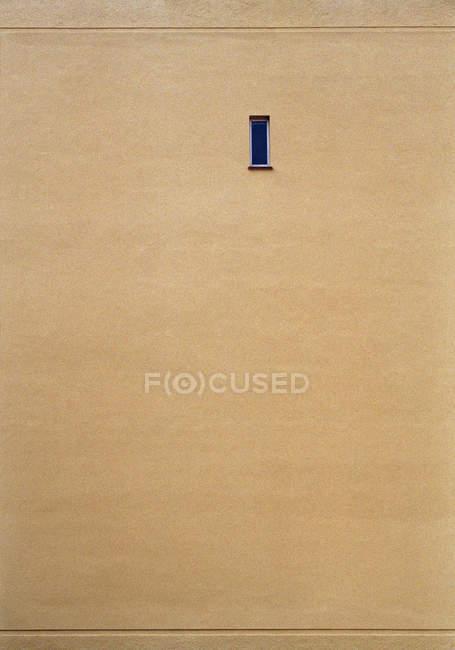 Cuadro completo de pared beige con una ventana estrecha - foto de stock