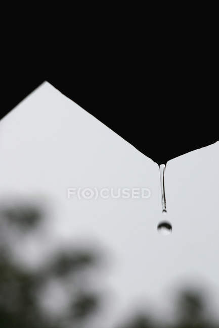 Drop of water falling from roof's edge — Stock Photo