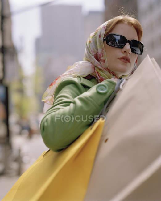 Mulher carregando sacos de compras e cruzando uma rua da cidade — Fotografia de Stock