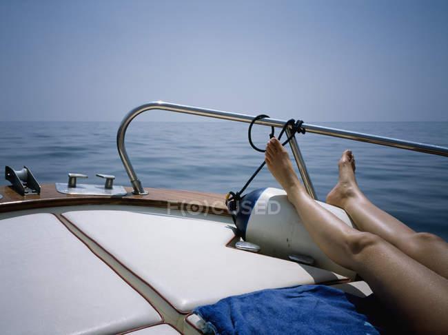 Crop female legs sunbathing on boat deck — Stock Photo