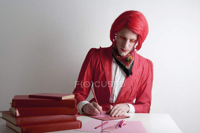 Drag queen sitting at desk with red books and writing on paper — Stock Photo