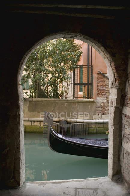 Обтинання гондоли на каналі видно через арці — стокове фото