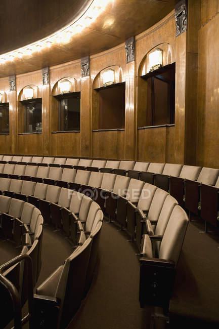 Строк пустых кресел в освещенной театральный зал — стоковое фото