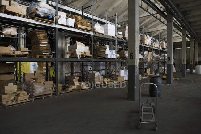 Interior view of warehouse with shelves and empty trolley — Stock Photo