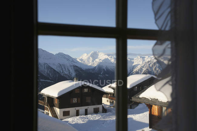 View through window to idyllic cottages at ski resort — Stock Photo