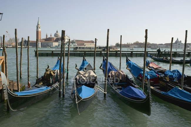 Row of gondolas moored to post Venice canal — Stock Photo