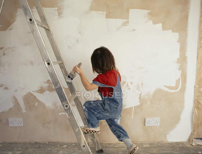 Un ragazzo che tiene un pennello mentre sale su una scala — Foto stock