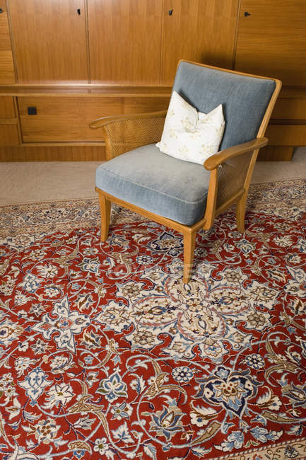 Retro chair on Persian rug in living room — Stock Photo