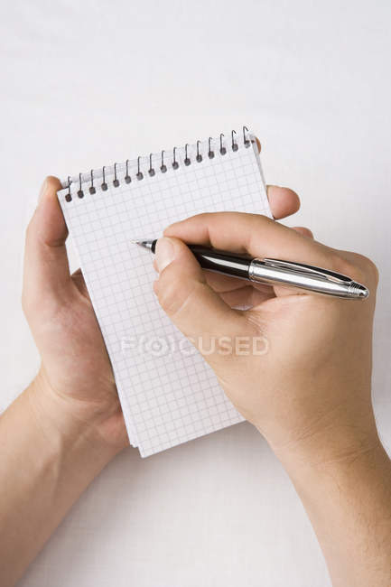 Crop hands writing in blank notebook — Stock Photo