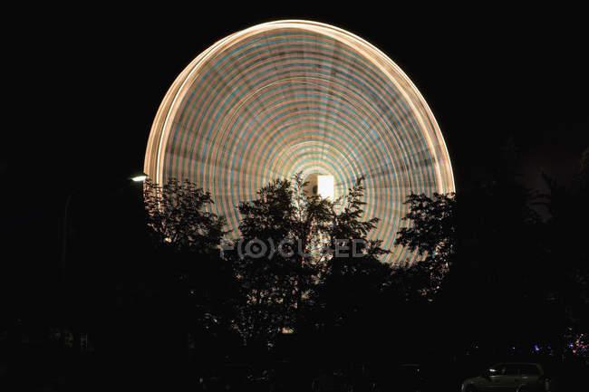 Tir longue exposition de la grande roue illuminée de nuit — Photo de stock