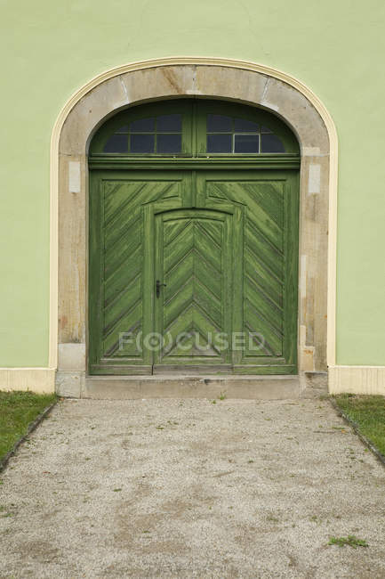 Exterior of green wall with old wooden doorway — Stock Photo