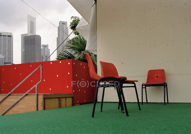 Plastic chairs on terrace with cityscape behind\ — Stockfoto