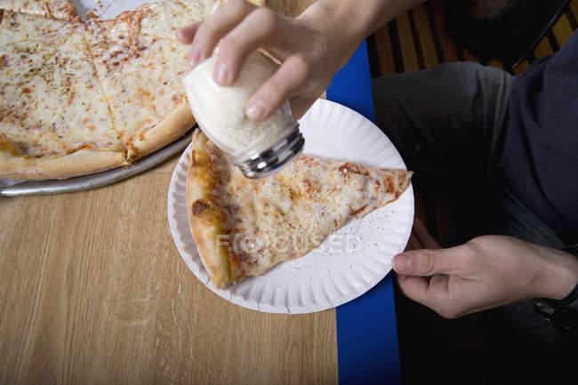 Person gießt Salz auf ein Stück Pizza — Stockfoto