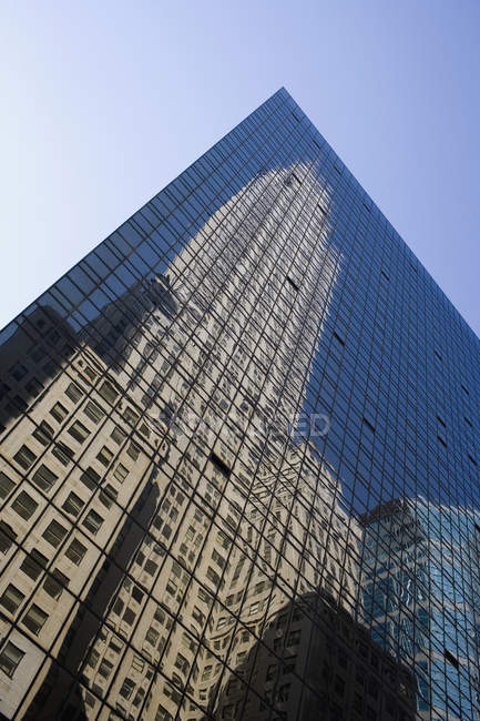 Bottom view of building reflected in facade of skyscraper — Stock Photo