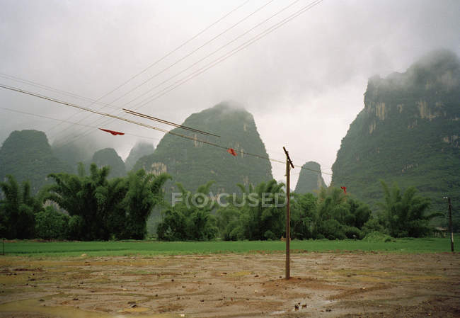 Electricity pylons and power lines over rock formations — Stock Photo