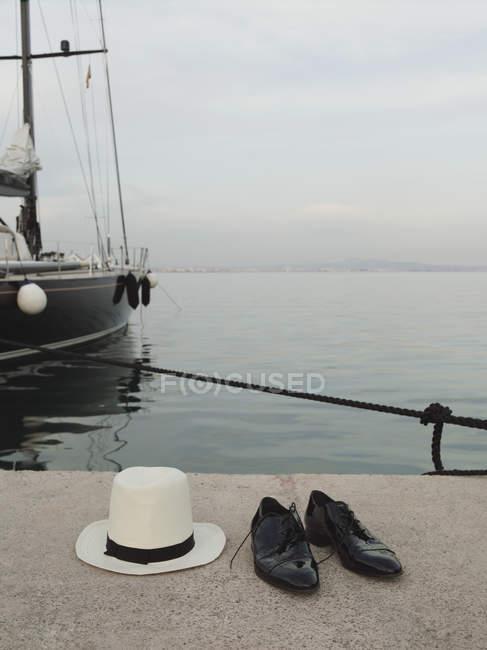 Cappello Panama e paio di scarpe ai bordi del molo — Foto stock