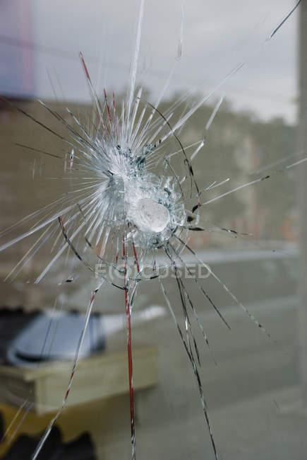 Close up view of broken window reflecting street — Stock Photo