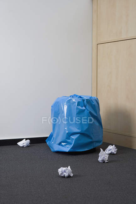 Wastepaper bin with crumpled paper on floor — Stock Photo