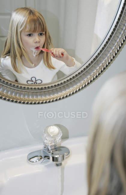 Giovane ragazza lavarsi i denti in un bagno — Foto stock