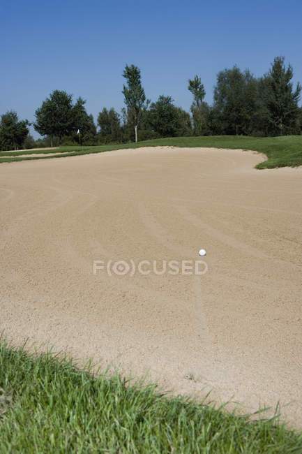 Boule de golf dans le bunker de sable au terrain de golf — Photo de stock