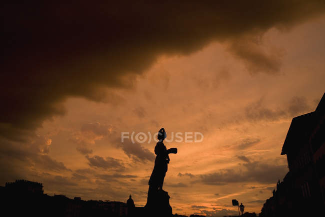 Silhouette of statue under tough cloudy sky — Stock Photo