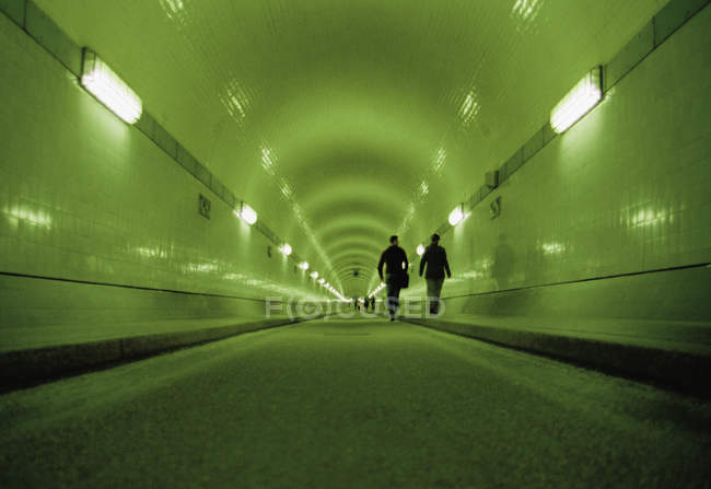 Surface level view of illuminated tunnel with pedestrians — Stock Photo