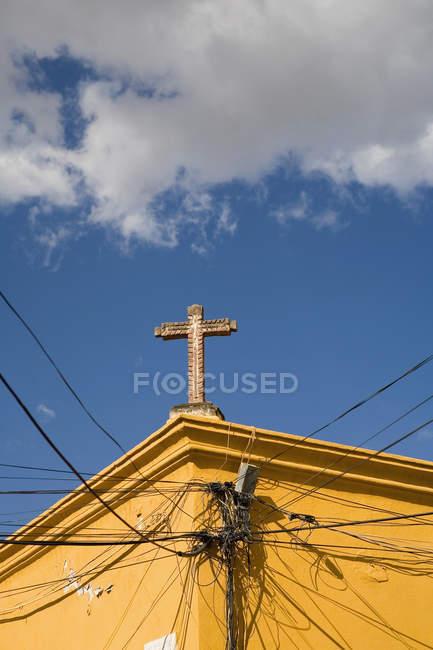Linee di alimentazione collegato alla facciata della Chiesa con croce — Foto stock
