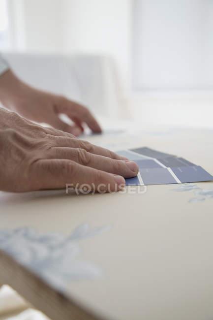 Couper les mains en comparant les échantillons de couleur au papier peint — Photo de stock