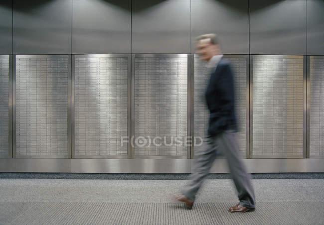Blurred man walking along safety deposit boxes — Stock Photo