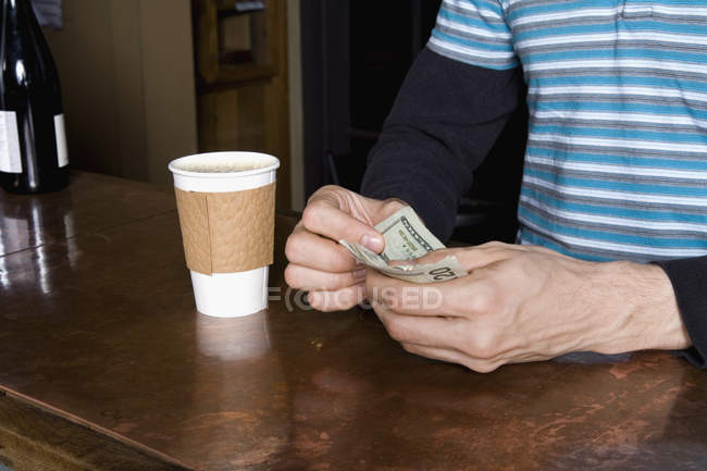 Cropped image of man paying for take-away coffee — Stock Photo
