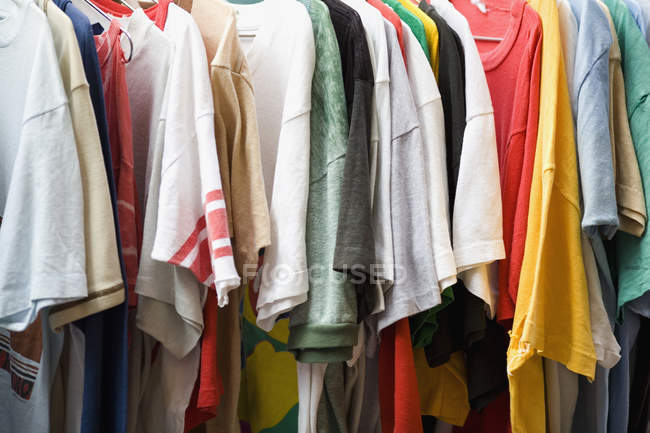 Full frame shot of various t-shirts hanging in row on rack — Stock Photo