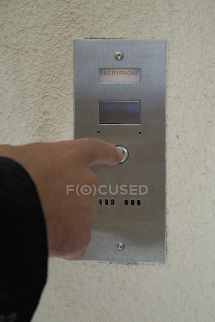 Recadrer la main masculine en appuyant sur le bouton interphone — Photo de stock