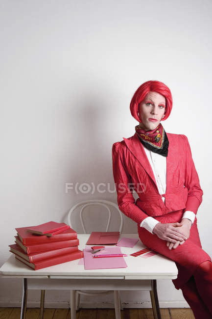 Drag queen posing on a desk with red books — Stock Photo