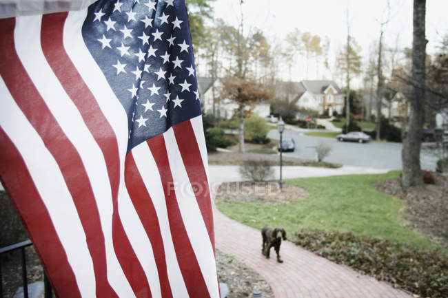 American flag in front yard of suburban house — Stock Photo
