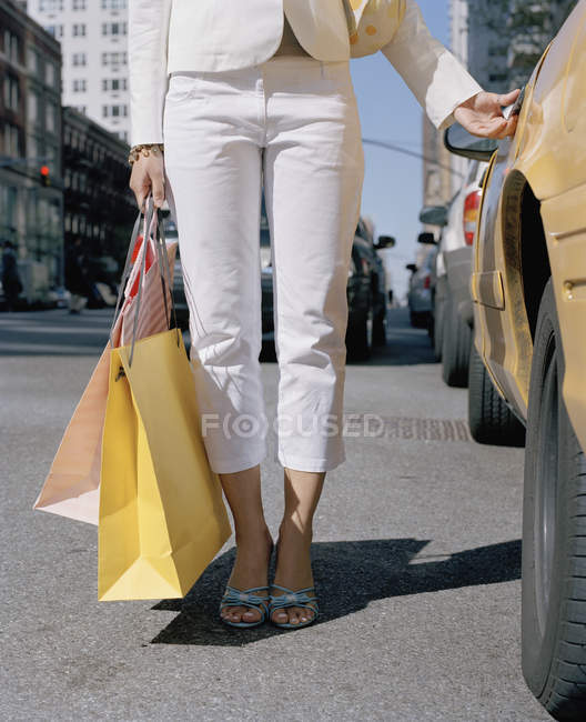 Woman holding shopping bags by a taxi — Stock Photo